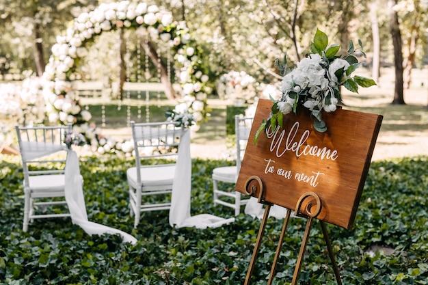 Tavola di legno con testo di benvenuto al nostro evento a un matrimonio in corridoio