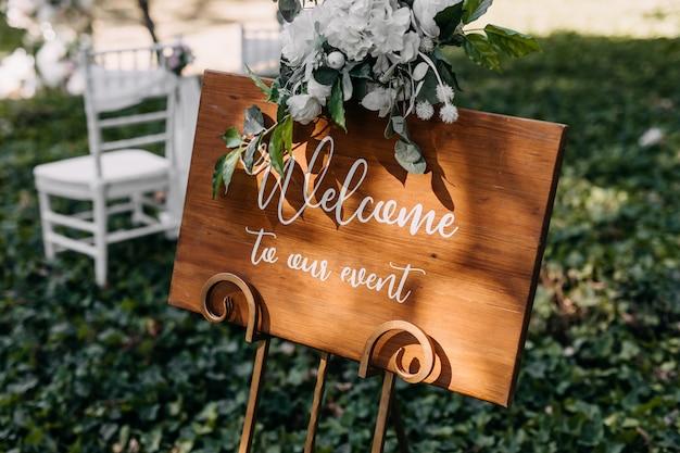 Tavola di legno con testo di benvenuto al nostro evento durante una cerimonia di matrimonio