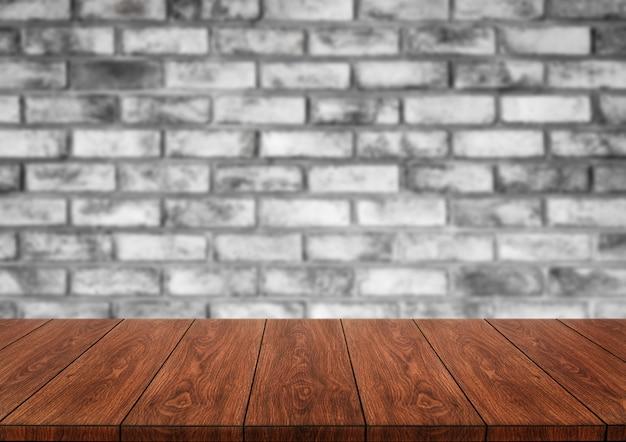 Tavola di legno davanti al fondo della sfuocatura del muro di mattoni.