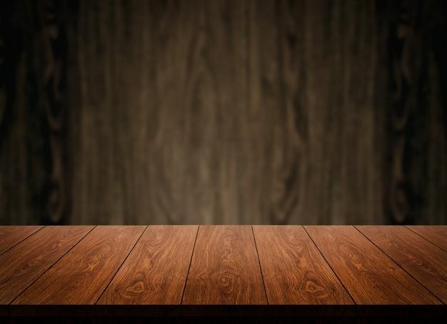 Tavola di legno davanti al fondo di legno della sfuocatura della parete.