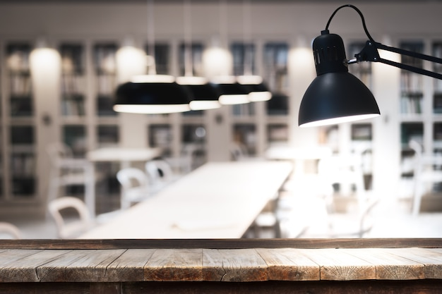 Tavola di legno davanti alla lampada da tavolo interna decorativa che appende sulla parete e sul soffitto nella sala.