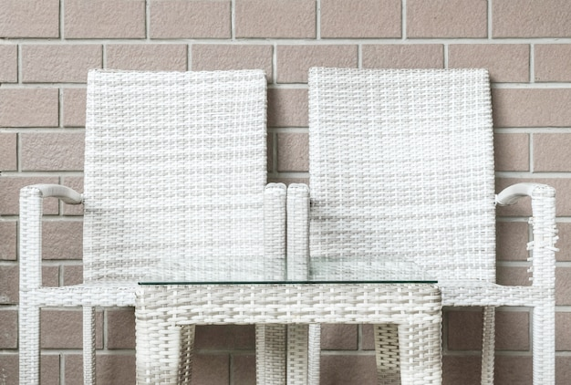 Tavola di legno del tessuto del primo piano e sedia di legno del tessuto sul fondo marrone vago di struttura del muro di mattoni