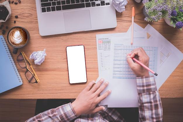 Tavola di legno dell'ufficio con l'uomo d'affari che controlla la carta di rapporto, schermo in bianco sul cellulare, vista da sopra la tavola.