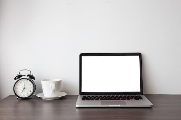 Tavola di legno dell'ufficio con lo schermo in bianco sul computer portatile, sul taccuino e sulla tazza di caffè calda, retro orologio nero sul fondo del cemento bianco.