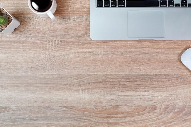 Tavola di legno funzionante di tecnologia con il computer portatile e la tazza di caffè