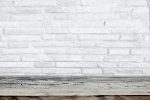Tavola di legno in bianco con il fondo bianco del muro di mattoni