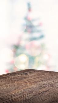 Tavola di legno marrone di angolo vuoto con il fondo astratto della sfuocatura della luce della corda della decorazione dell'albero di natale