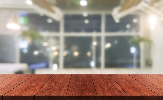 Tavola di legno nel fondo della sfuocatura del ristorante moderno