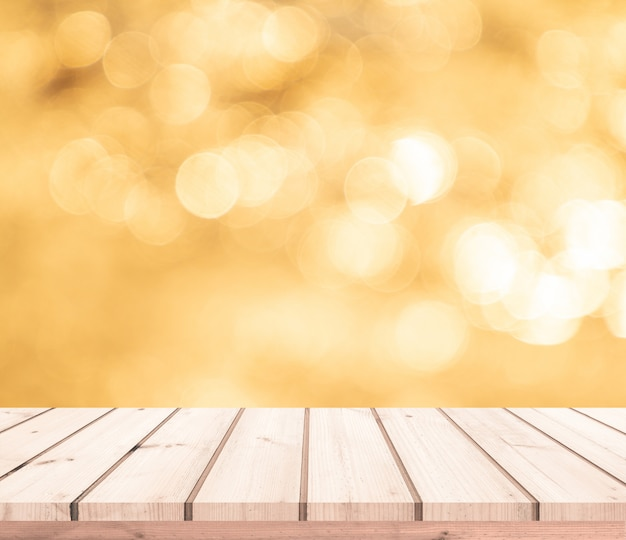 Tavola di legno o pavimento di legno con il fondo astratto del bokeh dell'oro per l'esposizione del prodotto