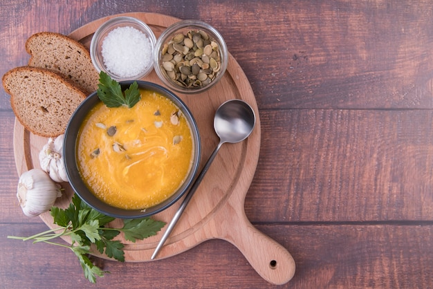Tavola di legno riempita con ciotola di zuppa e ingredienti