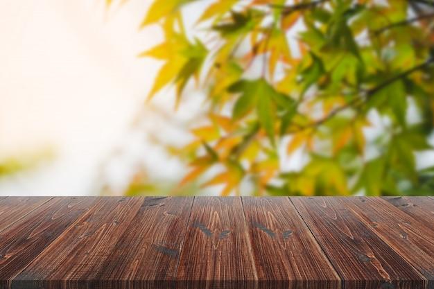 Tavola di legno sopra fondo vago, tavola di legno vuota di prospettiva sopra il fondo dell'albero di acero di defocus