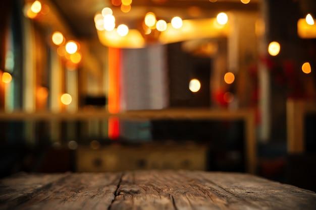 Tavola di legno sul fondo della sfuocatura del club o del ristorante