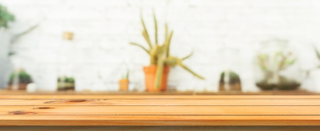 Tavola di legno tabella vuota sfocata sfondo. prospettiva tavolo di legno marrone su sfocatura in sfondo caffè. banner panoramico - può essere utilizzato come modello per la visualizzazione o la progettazione di prodotti di montaggio.
