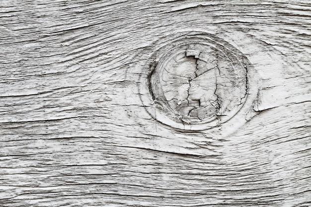 Tavola di legno verniciata grigia con un nodo.