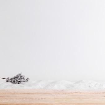 Tavola di legno vicino al ramoscello della pianta su mucchio di neve