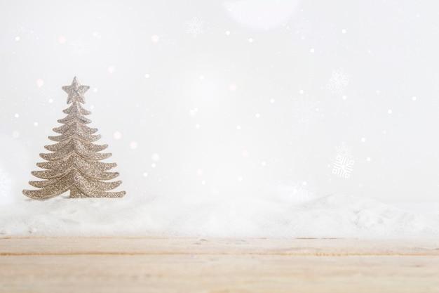 Tavola di legno vicino all'albero di natale del giocattolo sul mucchio di neve