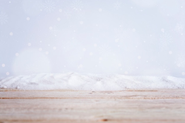 Tavola di legno vicino mucchio di neve e fiocchi di neve cadenti