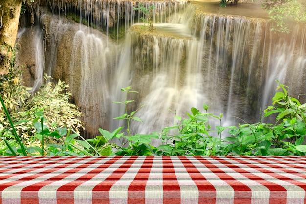 Tavola di legno vuota con bella scenografia della cascata e foglie verdi.