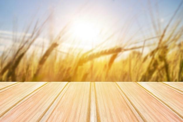 Tavola di legno vuota con erbe sfocate, grano sullo sfondo