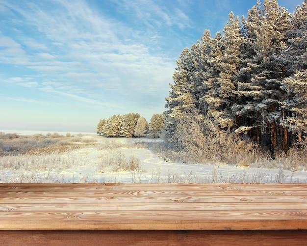 Tavola di legno vuota contro un paesaggio invernale.