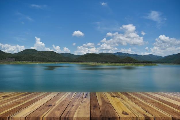 Tavola di legno vuota di prospettiva sulla cima sopra la diga e montagna con cielo blu nella priorità bassa
