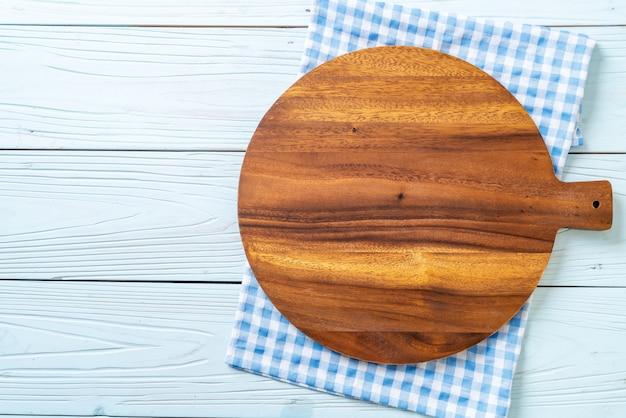 Tavola di legno vuota di taglio con un panno da cucina