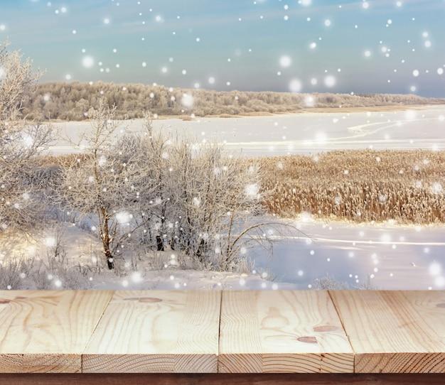 Tavola di legno vuota sul paesaggio invernale di sfondo.