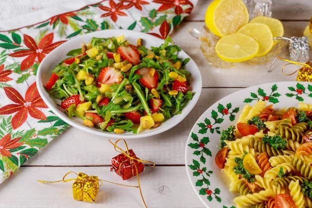 Tavola di natale con insalata, rucola fresca, fragole e pasta rotini.
