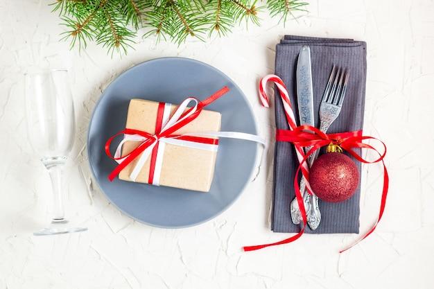 Tavola di natale impostazione posto con rami di abete, tovagliolo, forchetta, coltello, palla, piatto, bastoncini di zucchero, regalo e vetro.