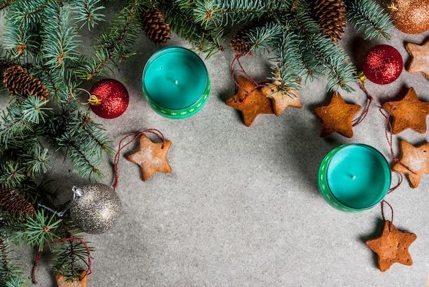 Tavola di natale, per biglietto di auguri. biscotti della decorazione di natale, delle candele, dell'albero di abete e del pan di zenzero sulla tavola di pietra grigia. vista dall'alto, .