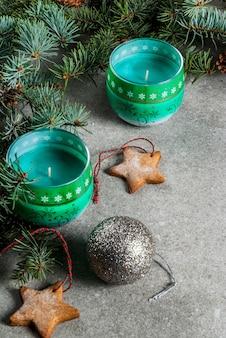 Tavola di natale, per biglietto di auguri. biscotti della decorazione di natale, delle candele, dell'albero di abete e del pan di zenzero sulla tavola di pietra grigia. .