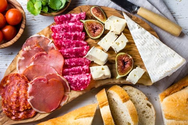 Tavola di olive con salame, prosciutto serrano, formaggio, noci e pane ciabatta