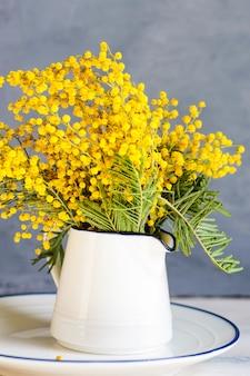 Tavola di primavera con fiori di mimosa