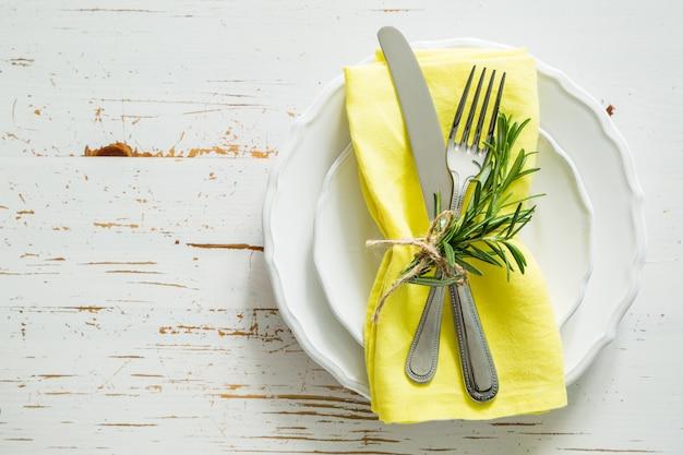 Tavola di primavera con rosmarino e tovagliolo giallo