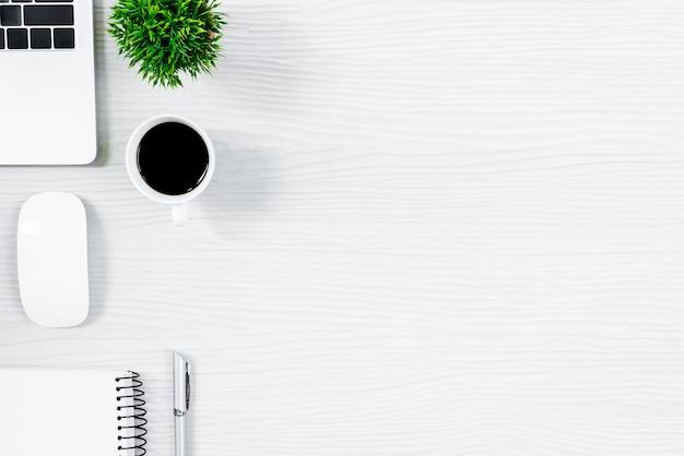 Tavola ed attrezzatura di legno bianche della scrivania per lavorare con caffè nero nella vista superiore e nel concetto piano del raggio.