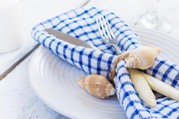 Tavola estiva ambientata in stile marino, decorata con conchiglie, clo