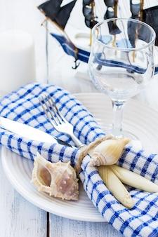 Tavola estiva ambientata in stile marino, decorata con conchiglie