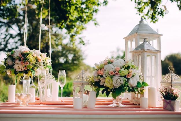 Tavola festiva meravigliosamente decorata in parco sul tramonto, cena romantica di nozze.