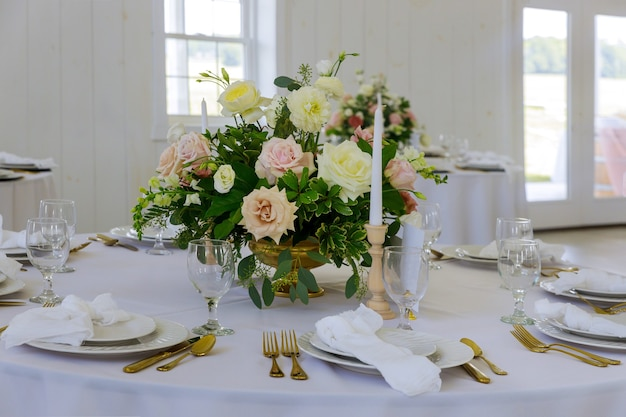 Tavola festiva servita per cena o festa con bicchieri e fiori.