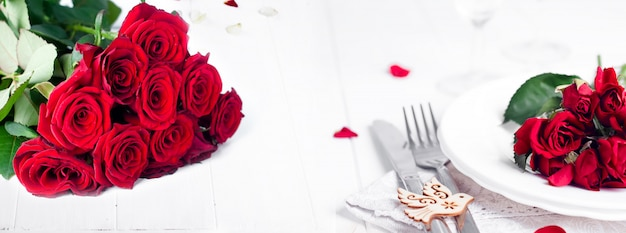 Tavola festosa con rose beige, bicchieri da vino, tovaglioli e posate,