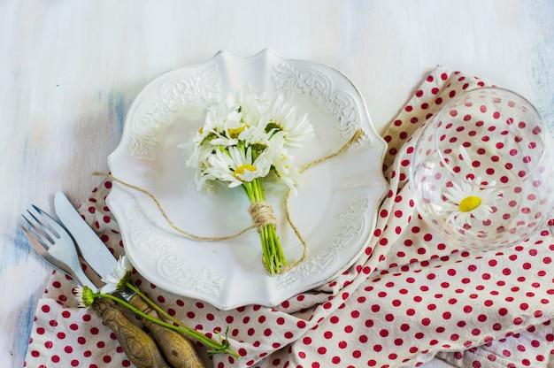 Tavola interna di tempo di primavera con fiori e posate