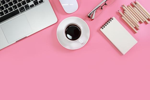 Tavola piana dell'area di lavoro di disposizione con il computer portatile sul rosa