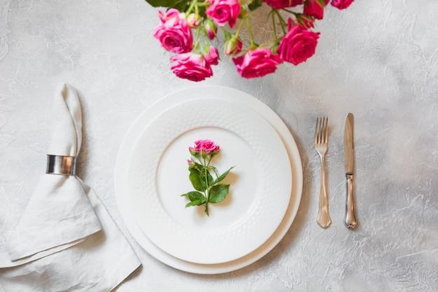Tavola romantica con bouquet di rose rosa e decorazioni. vista dall'alto.