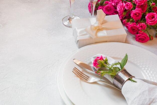 Tavola romantica con rose rosa, argenteria e decorazioni. vista dall'alto.