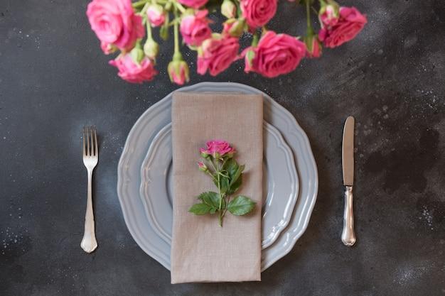 Tavola romantica con rose rosa come decorazione, stoviglie d'epoca, posate e decorazioni.