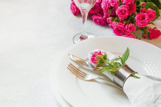 Tavola romantica con rose rosa come decorazione, stoviglie, posate e decorazioni. vista dall'alto.