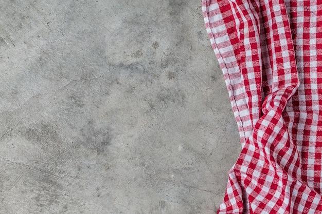 Tavola vuota coperta con la tovaglia controllata rossa overwared cemento sfondo della parete,