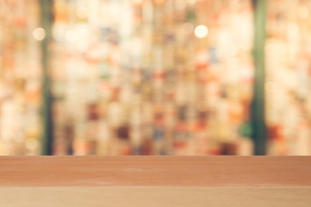 Tavola vuota del bordo di legno davanti a fondo vago. legno marrone di prospettiva sopra sfuocatura in caffetteria
