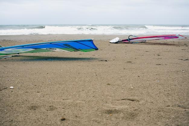 Tavole da windsurf nella sabbia di una spiaggia spagnola mentre i surfisti aspettano l'onda giusta.