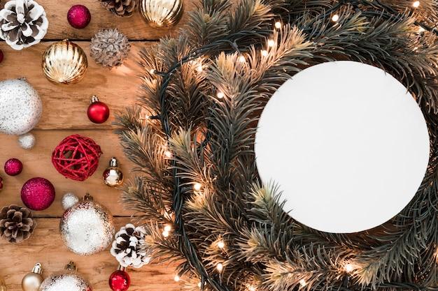 Tavoletta bianca tra ramoscelli di abete e decorazioni natalizie
